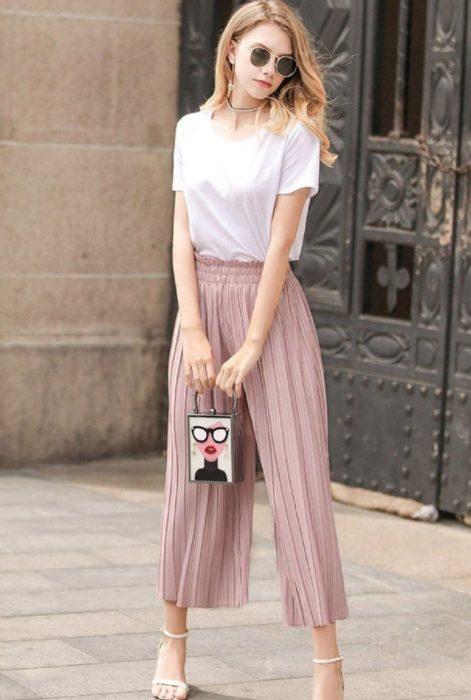 Chica usando unos pantalones culottes de color rosa y blusa blanca