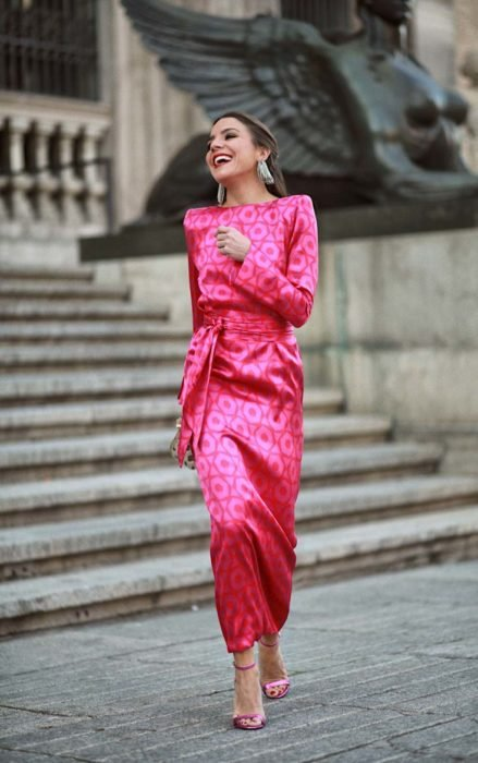 Chica caminando por la calle mientras usa un vestido de color rosa
