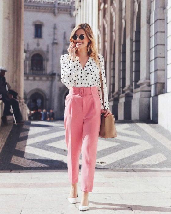 Chica usando un pantalón de color rosa con una blusa de lunares negros