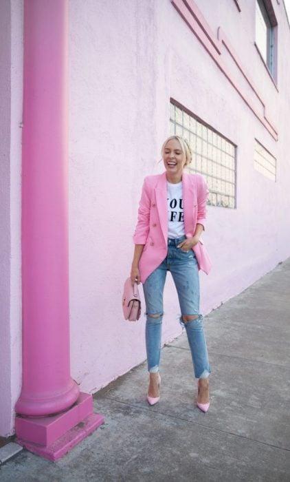Chica usando unos jeans con blusa blanca y blazer de color rosa