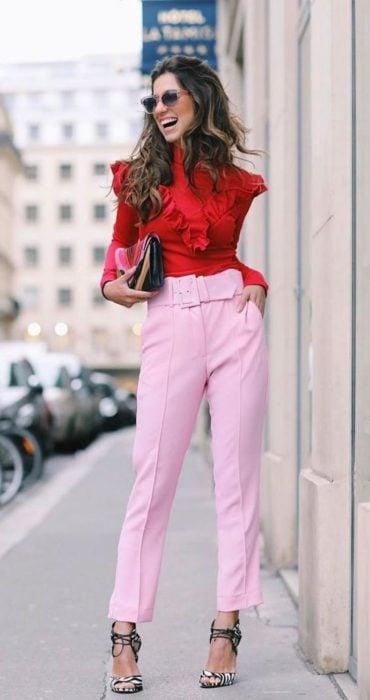 Chica usando unos pantalones de color rosa y una blusa de color rojo