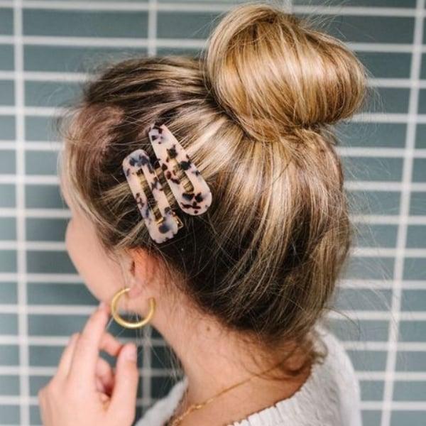 Chica con el cabello sujetado en un chongo y adornado con pinzas