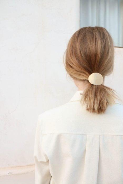 Chica usando el cabello en una coleta y adornado con un broche de color dorado
