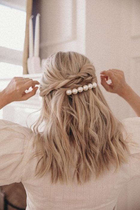 Chica con el cabello sujetado en media coleta y adornado con broche de perlas