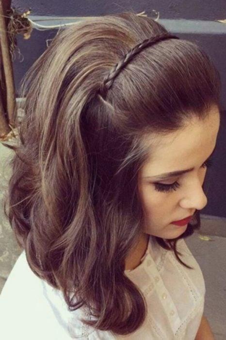 Chica con el cabello en ondas sujetado con una trenza como diadema