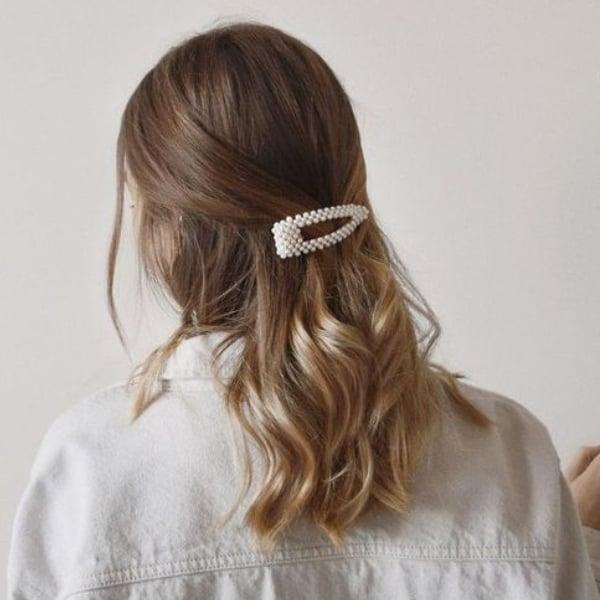 Chica con el cabello hasta el hombro recogido con un broche