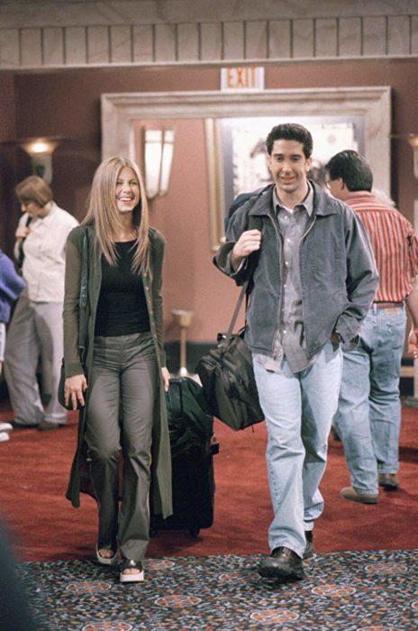 Escena de Friends con Rachel y Ross caminando por un pasillo con maletas, ella viste de gris con negro y él mezclilla con gris