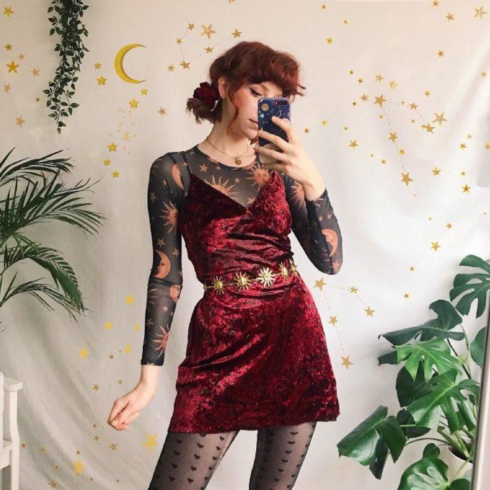 Ropa de constelaciones; chica pelirroja con blusa de estrellas, soles y lunas, con vestido rojo de terciopelo de tirantes y escote en v, con cinto de sol y medias de corazones