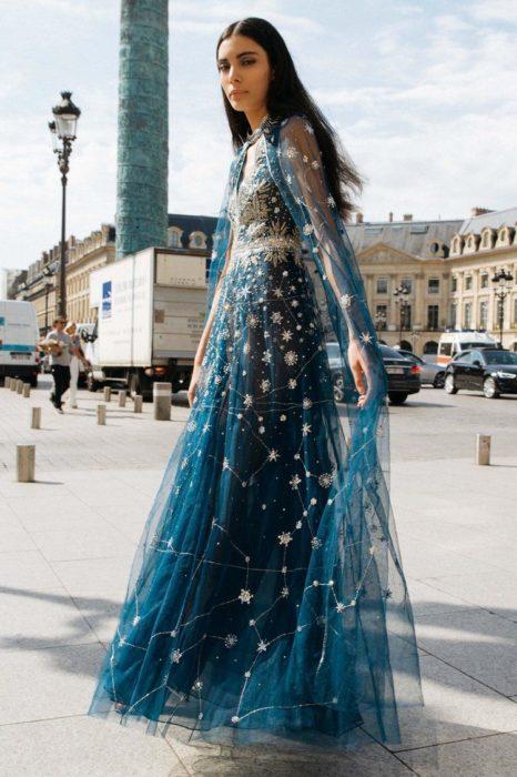 Ropa de constelaciones; mujer caminando en la calle con vestido de gala azul de tela de gasa con estampado de universo y estrellas