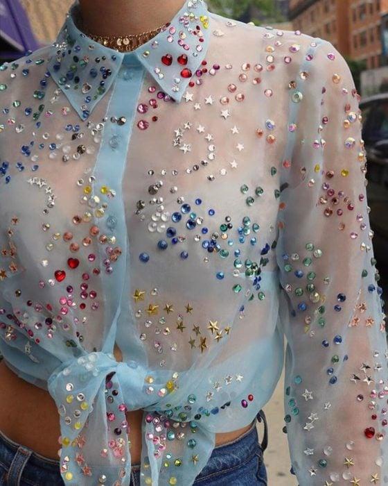 Ropa femenina de Lirika Matoshi; blusa de botones de tela semitransparente azul con pedrería