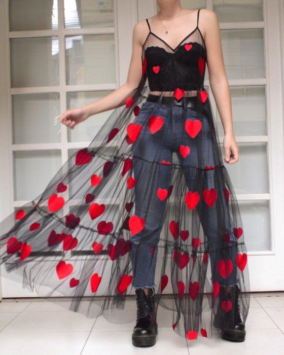 Ropa femenina de Lirika Matoshi; vestido de tela de encaje semitransparente de color negro con corazones rojos, de tirantes y con pantalón de mezclilla y crop top abajo