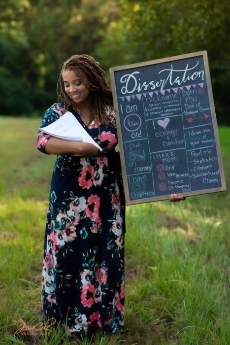 Eve Humphrey tomando una foto junto a su doctorado y un cartel de felicitación