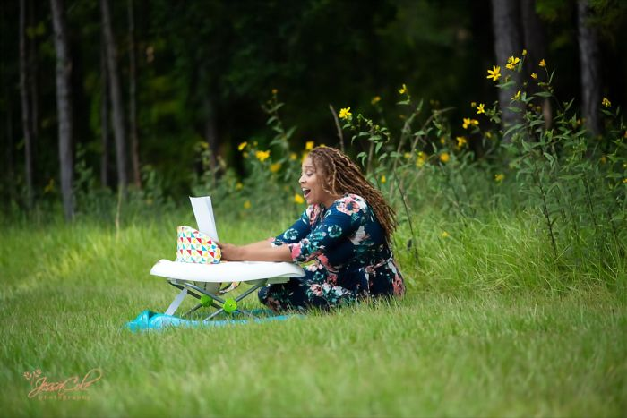 Eve Humphrey sentada en un jardín, sonriendo al mirar su tesis de doctorado finalizada