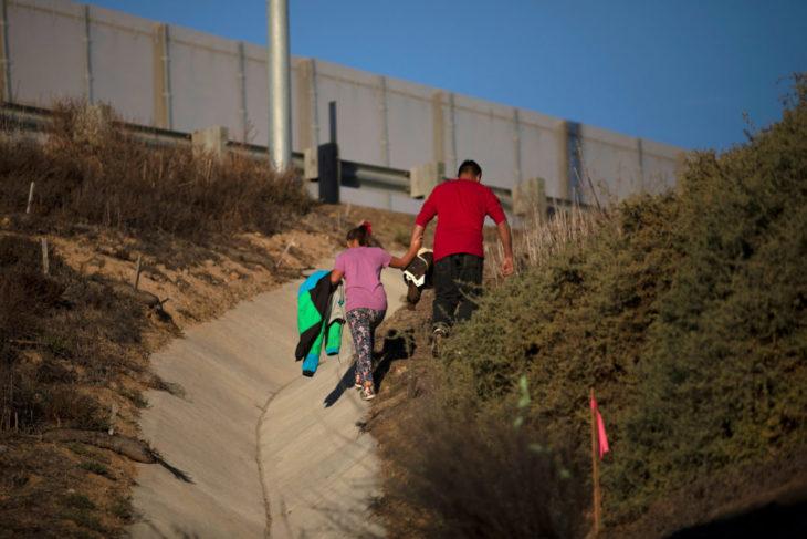 Un hombre lleva de la mano a su hija a un lado del muro fronterizo entre México y Estados Unidos