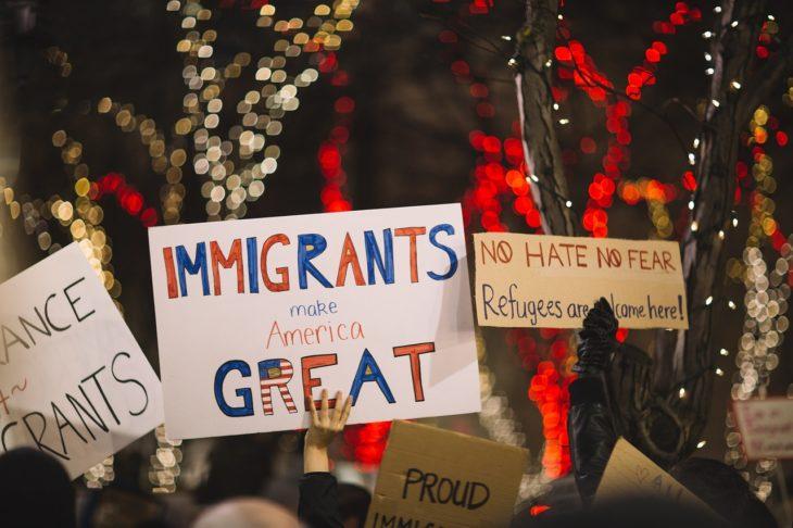 una manifestación pro inmigrantes con carteles que dicen que los inmigrantes harán a America grandiosa otra vez