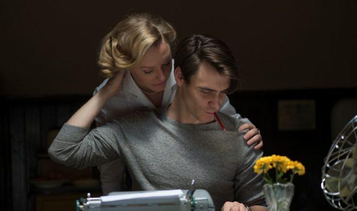 un hombre revisa algunos papeles sobre su escritorio y una mujer está atrás de él abrazándolo viendo los papeles