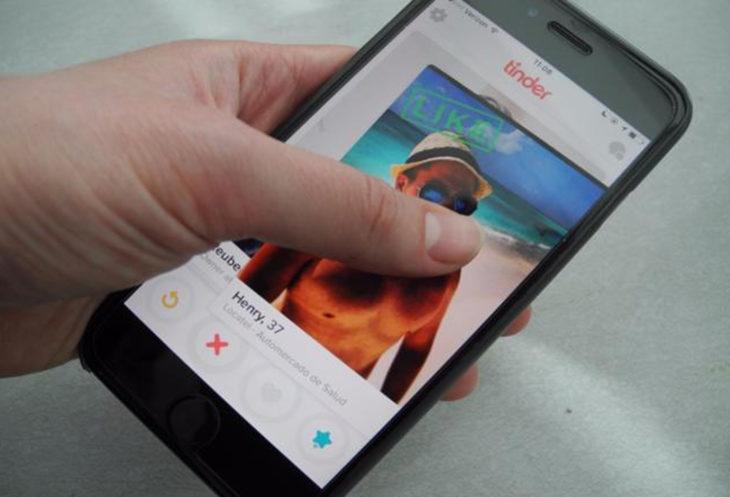 fotografía de un teléfono que tiene una imagen de Tinder en la pantalla