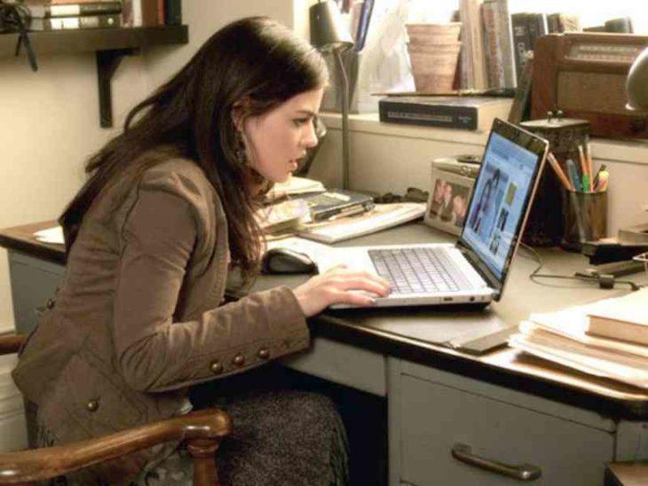 Una mujer ve una fotografía de una pareja en una computadora sobre un escritorio