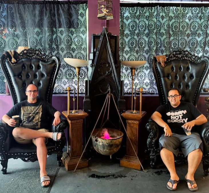 Hombres sentados en sillas grande sy oscuras en Steamy Hallow