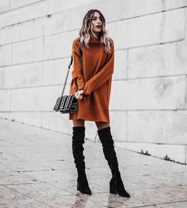 Chica de cabello rubio usando suéter oversized anaranjado como vestido de otoño con botas negras largas de tacón cuadrado