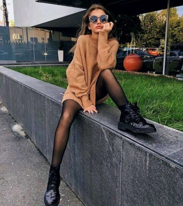 Chica sentada en la calle con lentes de sol, suéter largo como vestido de otoño, medias negras y botas de trabajo Dr. Martens brillantes