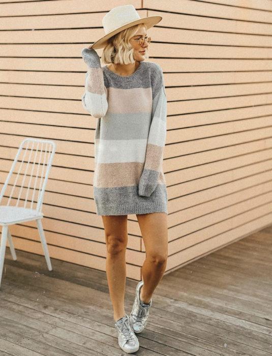 Fotografía estilo vintage de mujer de cabello rubio y corto arriba de los hombros, con lentes de sol cuadrados y sombrero caqui, con suéter oversized con franjas grises, beiges y blancas; vestido de otoño