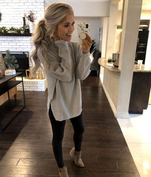 Mujer romándose selfie frente al espejo con suéter grande como vestido de otoño, con leggins negros y botines