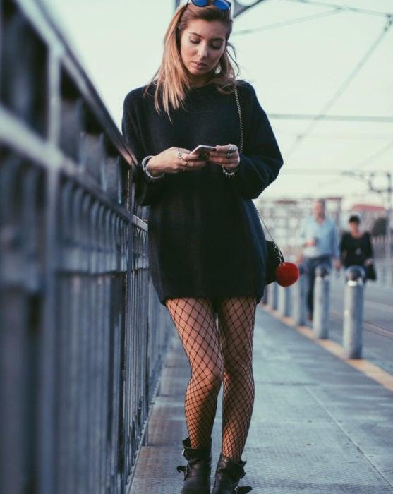 Mujer viendo su celular en la calle, usando un suéter oversized negro como vestido de otoño, con medias de red y botines negros con hebillas