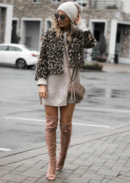Mujer rubia con gorro de invierno, usando suéter oversized como vestido de otoño, con abrigo felpudo de animal print y botas de gamuza largas sin punta