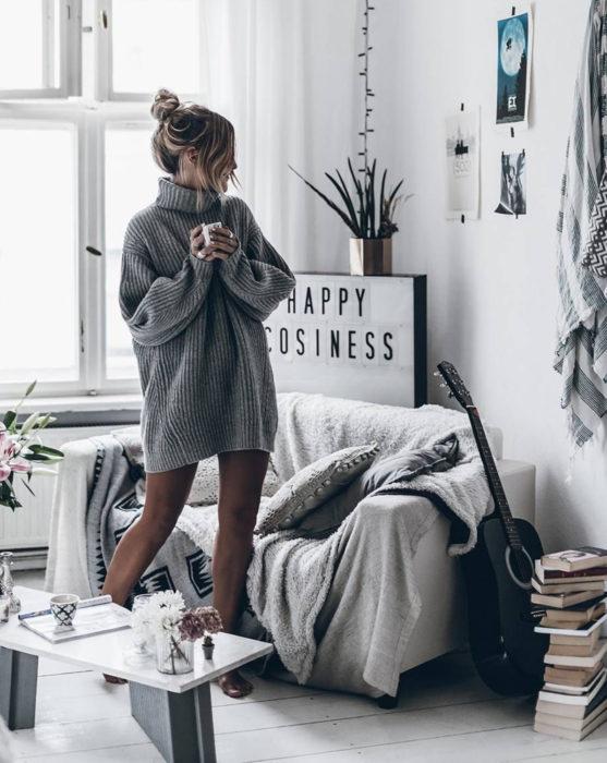 Mujer con peinado de chongo despeinado, usando suéter gris oversized como vestido de otoño, bebiendo una taza de café en su casa junto a su sillón con guitarra acústica negra y una pila de libros