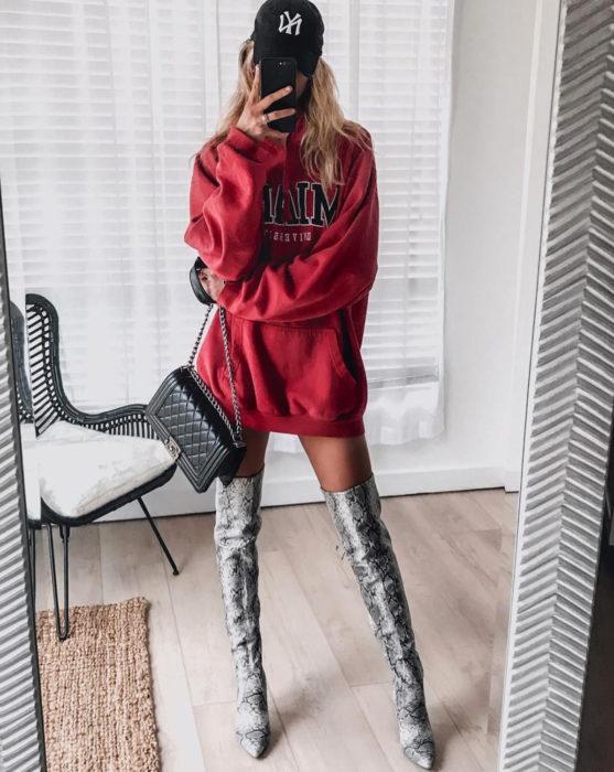 Mujer rubia tomándose selfie frente al espejo, con sudadera roja oversized como vestido de otoño, con botas largas de animal print de serpiente gris