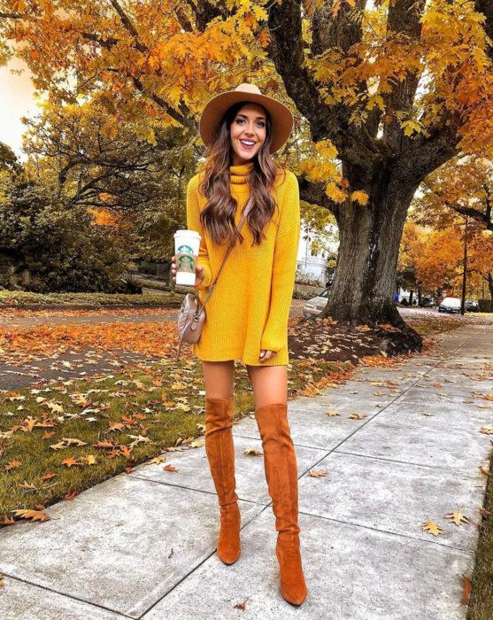 Chica en la calle frente a un árbol de hojas amarillas, usando un sombrero, botas largas anaranjadas y suéter holgado como vestido de otoño