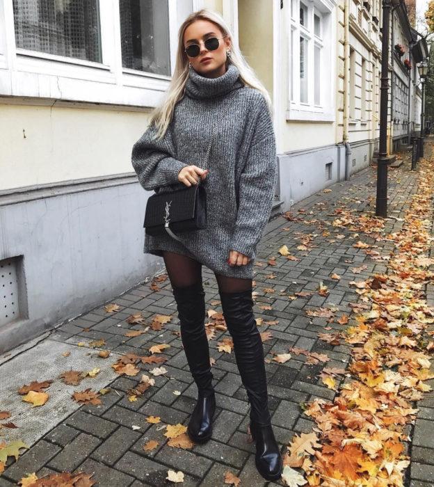Chcia de cabello rubio y largo caminando en la calle con hojas en el suelo, vistiendo un suéter gris y grande como vestido de otoño con medias y botas largas y negras