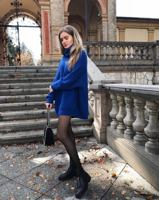 Chica rubia en escaleras con suéter oversized azul rey como vestido de otoño, con medias y botines negros