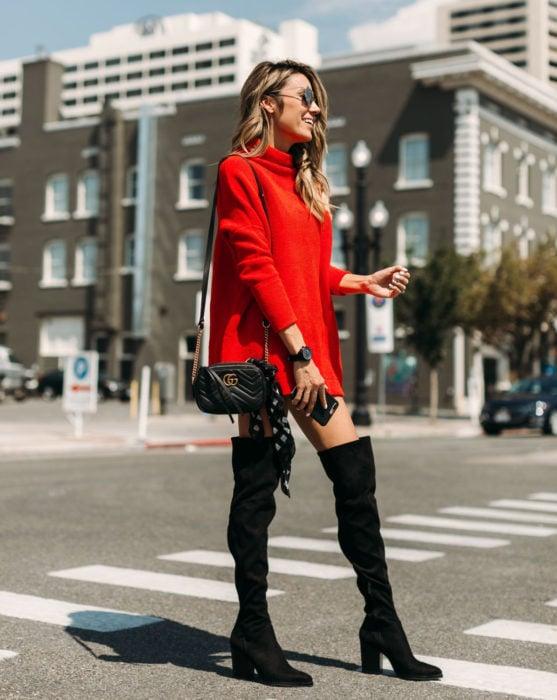 Mujer rubia en la calle, sonriendo y vistiendo un suéter oversized rojo como vestido de otoño con botas negras y largas de gamuza
