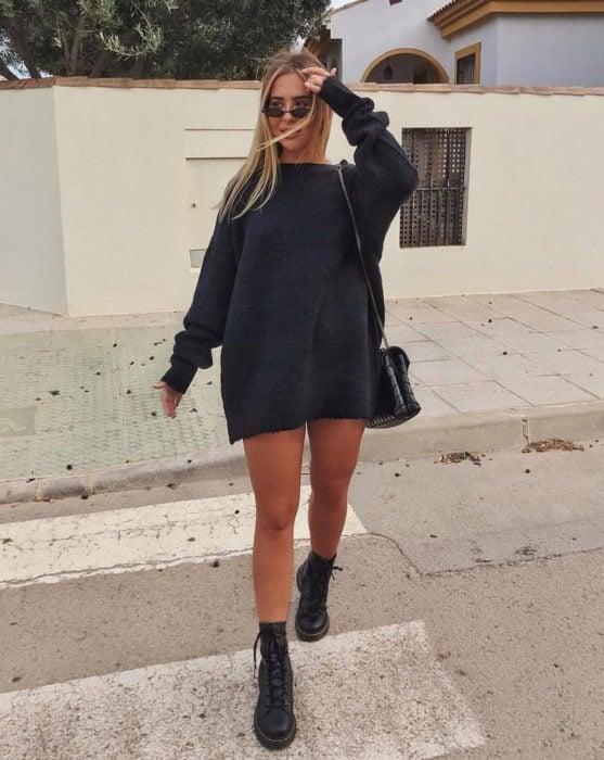 Chica cruzando la calle, con suéter oversized gris como vestido corto de otoño, con botas de trabajo Dr. Martens
