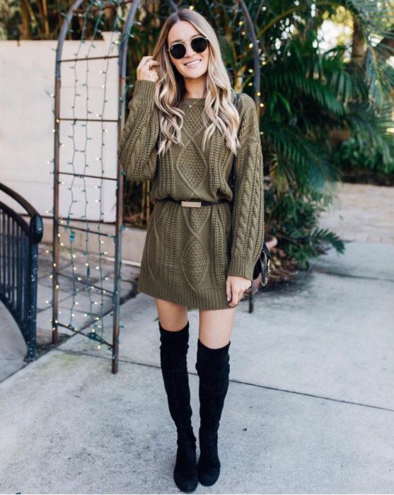 Chica de cabello rubio, largo y ondulado usando un suéter de abuelita grande y tejido de color verde militar como vestido de otoño, con cinto y botas negras y largas