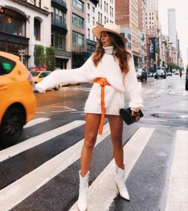 Chica en cruce peatonal haciéndole la parada a un taxi, usa suéter blanco grande como vestido corto de otoño, con cinturón anaranjado y botas puntiagudas y blancas, con sombrero y bolsa de mano