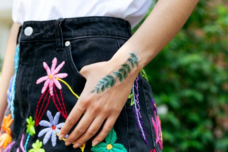 Chica mostrando un tatuaje temporal de Tessa Perlow con efecto bordado en forma de hojas d eeucalipto en la palma de la mano