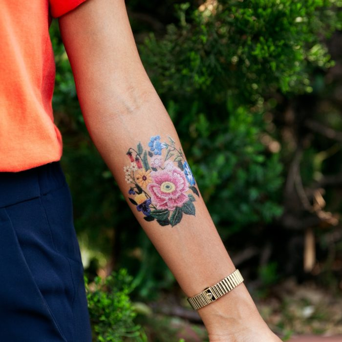 Chica mostrando su antebrazo con un tatuaje temporal de Tessa Perlow con efecto bordado en forma de rosa, rosa