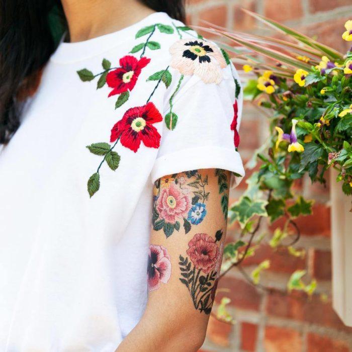 Chica mostrando su brazo con un tatuaje temporal de Tessa Perlow con efecto bordado en forma de flores de colores