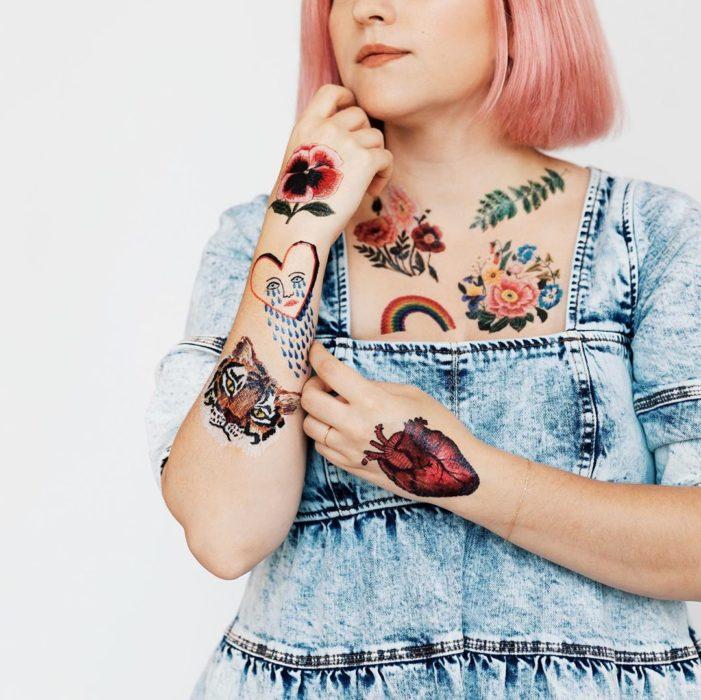 Chica modelando tatuajes con flores, corazones realistas y arcoiris, tatuajes temporales de Tessa Perlow