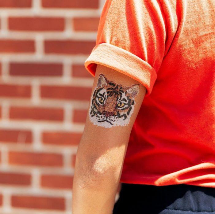 Mujer mostrando un tatuaje temporal de Tessa Perlow con efecto bordado con rosto de tigre bengala