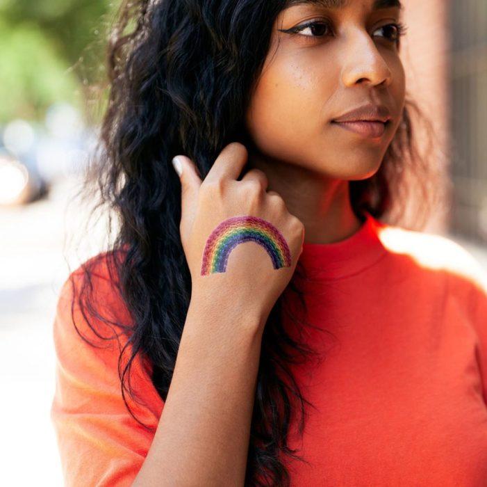 Chica acariciando su cabello y mostrando un tatuaje temporal de Tessa Perlow con efecto bordado en forma de arcoíris