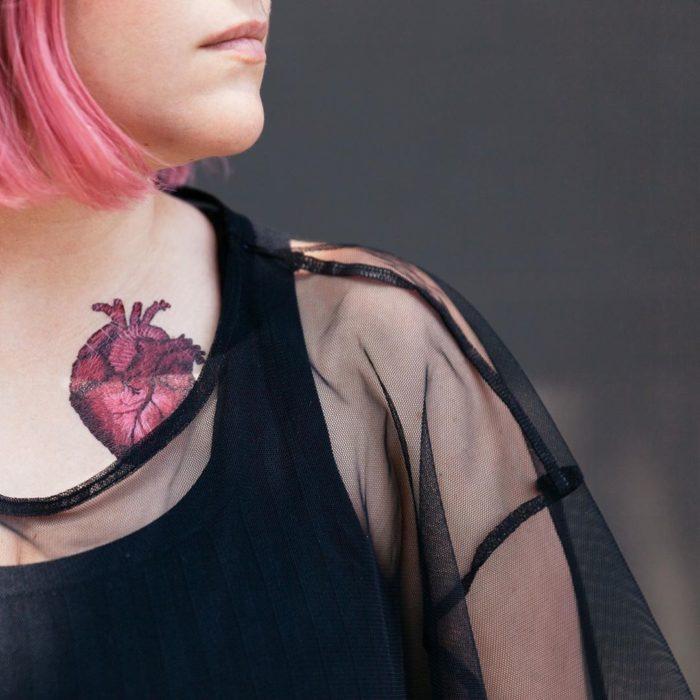 Chica mostrando un tatuaje temporal de Tessa Perlow con efecto bordado en forma de corazón realista
