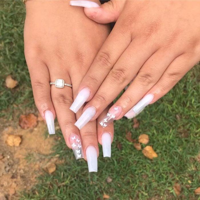 Chica con unas uñas de mariposa en color blanco con transparencias