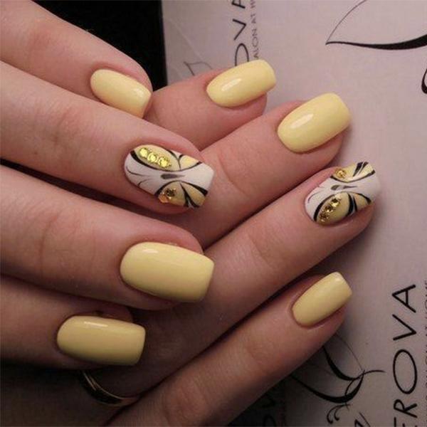 Chica con unas uñas de mariposa en colores amarillos con negro