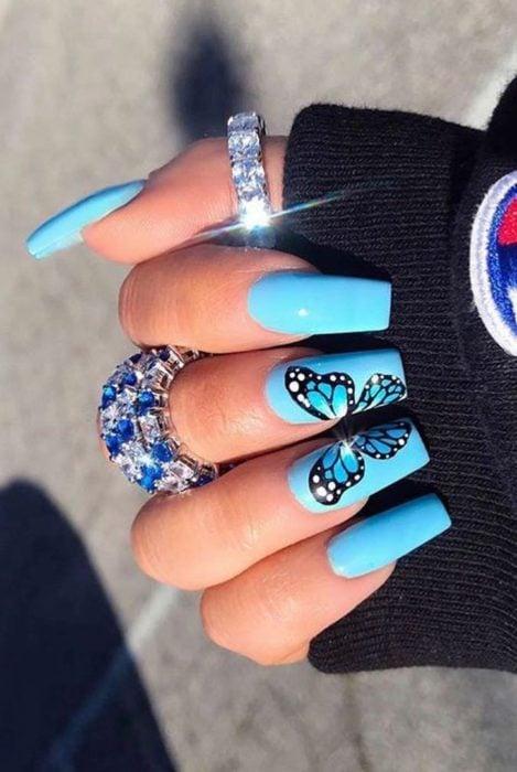 Chica con unas uñas de mariposa en colores azul marino