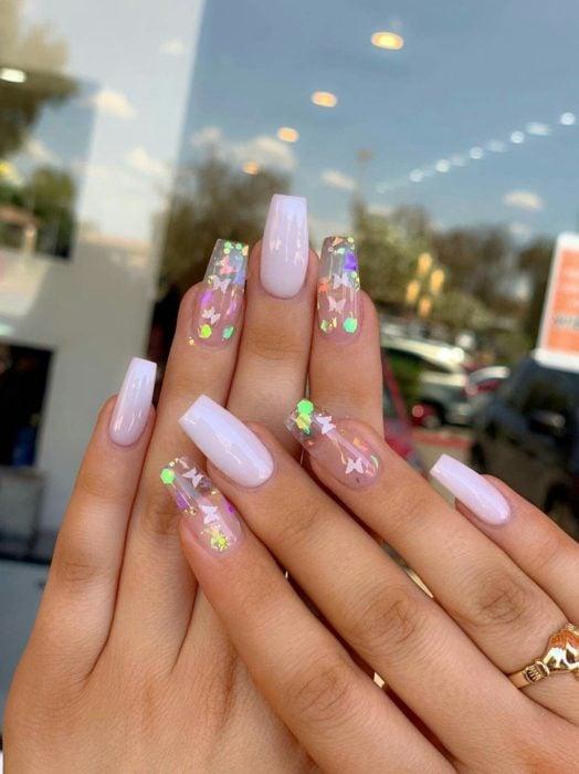 Chica con unas uñas de mariposa en colores lila y detalles tornasol
