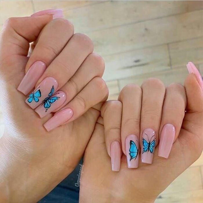 Chica con unas uñas de mariposa en color nude con la mariposa en color azul electrico